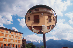 Circular mirror positioned in street,