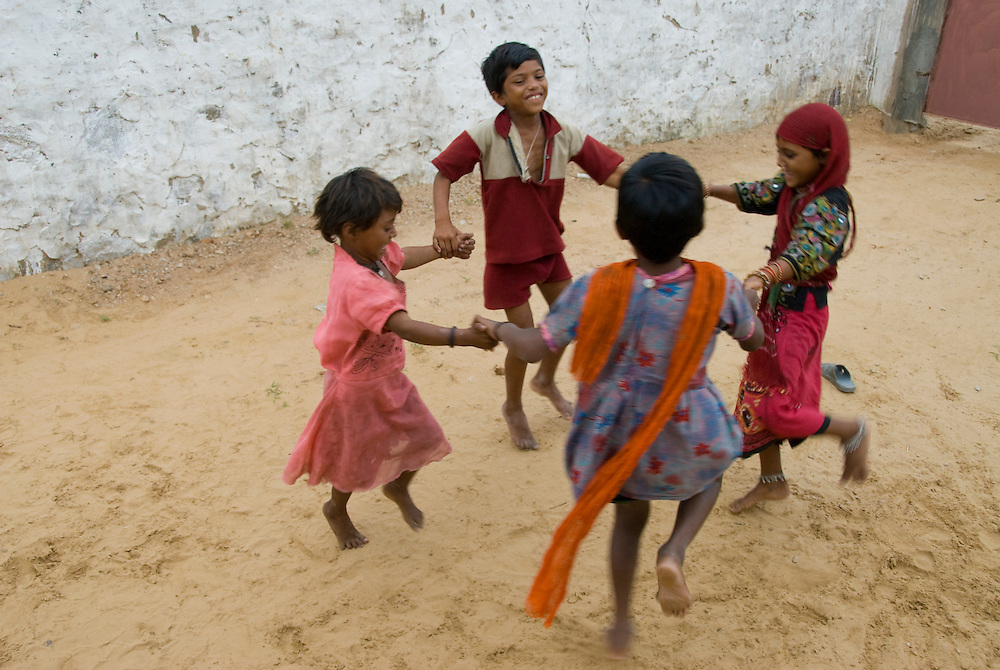 With little or no toys, these Rajasthani children amuse themselves in the backyard of their house in a desert village of Rajasthan (India)