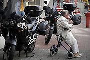 Nederland, Nijmegen, 20-7-2004..Een oudere vrouw leunt op haar rollator.Contrast met twee motoren achter haar. Hulpmiddel voor mobiliteit. ..Foto: Flip Franssen