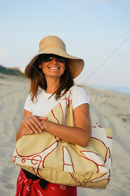 woman in a large sun hat holding a large bag on the beach in East Hampton,NY
