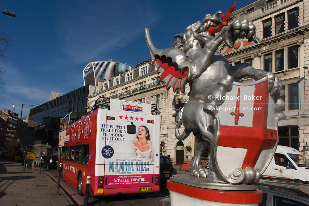 Bus rear advertising for Abba's West End musical Mamma Mia as it drives past a city boundary griffin.
