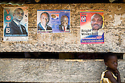 A girl stands by a wall plastered with posters promoting electoral candidates ahead of the presidential election in Afiaso, Ghana on Monday August 25, 2008.