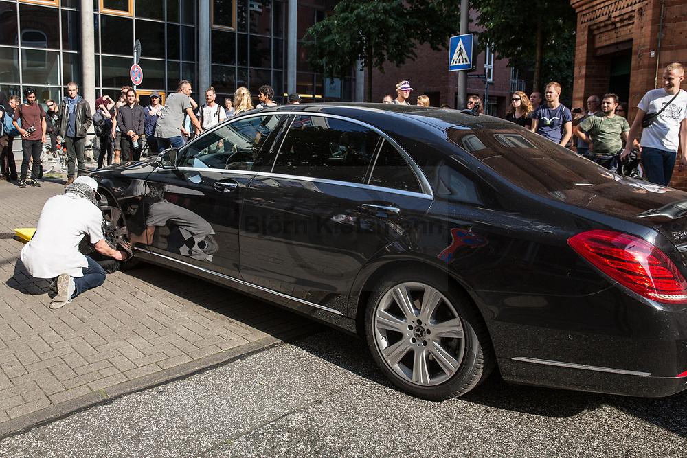 Hamburg, Germany - 07.07.2017<br /> <br /> An anti-G20 demonstrator empty the air from the tires of a blocked G20 convoy vehicle.<br /> <br /> Ein Anti-G20 Demonstant lasst die Luft aus den Reifen einem blockierten G20-Konvoi-Fahrzeug.<br /> <br /> Photo: Bjoern Kietzmann