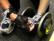 Bob Radocy of TRS Inc. attaches a prosthetic hand designed for weightlifting to a barbell at a gym in Boulder, Colorado August 21, 2009. Radocy designs and builds prosthetic attachments that allow amputee athletes to participate in multiple sports.  REUTERS/Rick Wilking (UNITED STATES)