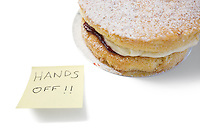 Sponge cake with 'hands off' sign on sticky notepaper