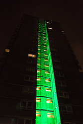 """London, UK. 14th June, 2018. The Green for Grenfell illuminations are lit at the Grenfell Tower and the twelve closest tower blocks (seen here Dixon House on the Silchester West Estate) on the first anniversary of the fire in a display intended to 'shine a light"""" of love and solidarity for all those affected and to raise awareness of the plight of those still without new homes after one year. Green for Grenfell is a community-led initiative in collaboration with tenants' and residents' associations and Grenfell United."""