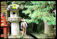 Groundskeeper in straw hat & purple gloves disappears into corner of Daiyuin-byo Shrine; Nikko. Japan