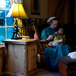 Cathy Kauffman, wearing a traditional mennonite clothing sits in a rocking chair holding Holly, her 15 month old adopted baby that is from the Marshall Islands at 5-Star Buildings in Cuba, Missouri on Tuesday, Sept. 27, 2016. (Photo by Keith Birmingham Photography)