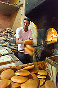 Baker prepares bread using a stove heated by the same furnaces which heat the hammans inside the medina, Marrakech, Morocco, 2016–04-16.