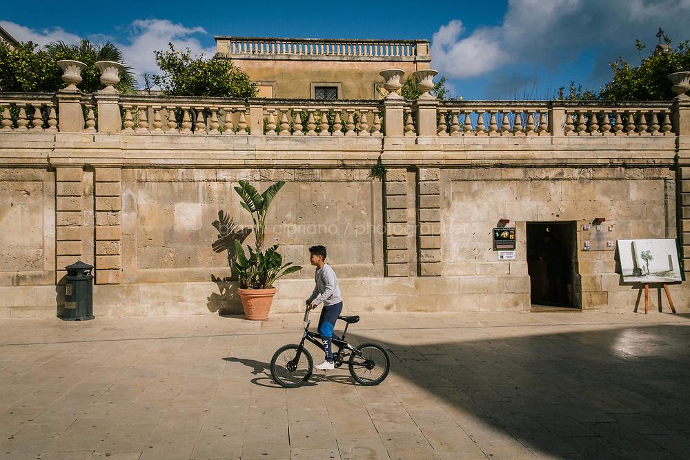 SIRACUSA (SR) - 22 MARZO 2018: Un ragazzino in bicicletta in Piazza del Duomo a Siracusa il 22 marzo 2018. <br /> <br /> Siracusa &egrave; considerata tra le citt&agrave; pi&ugrave; ospitali d'Italia.<br /> <br /> ###<br /> <br /> SIRACUSA, ITALY - 22 MARCH 2018: A child rides his bike in Piazza Duomo in Siracusa, Italy, on March 22nd 2018.<br /> <br /> Siacusa is considered one of the most coziest Italian cities.