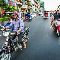 Jan 3, 2013 - Motorcyclists ride along a main street Preah Sisowath Quay along the Tonle Sap and Mekong Rivers of the Cambodian capital city of Phnom Penh.<br /> <br /> Story Summary: Amidst the feverish pace of Phnom Penh&rsquo; city streets, a workhorse of transportation for people and goods emerges: Bicycles, motorcycles, scooters, Mopeds, motodups and Tuk Tuks roam in place of cars and trucks. Almost 90 percent of the vehicles roaming the Cambodian capital of almost 2.3 million people choose these for getting about. Congestion and environment both benefit from the small size and small engines. Business is booming in the movement of goods and and another one million annual tourists in Cambodia&rsquo;s moto culture.
