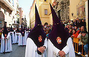 """Hermandad de San Benito de Sevilla, Seville, Andalusia, Spain...Semana Santa de Sevilla, Catholic Holy Week from Palm Sunday to Easter Sunday, is one of the most important traditional, cultural and spiritual events in Seville. The origins of the penitential Holy Week in Seville are to be found in the late Middle Ages. At the heart of Semana Santa are the brotherhoods (Hermandades y Cofradias de Penitencia).  At the centre of each procession are the pasos, an image or set of images set atop a movable float of wood. When a brotherhood has three pasos, the first one would be a sculpted scene of the Passion or an allegorical scene, known as a misterio (mystery); the second an image of Christ and the third an image of the Virgin Mary known as a dolorosa. Many sculptures are of great antiquity and considered artistic masterpieces. A total of 60 penitential processions are organized by hermandades and cofradías, religious brotherhoods. Members precede the pasos dressed in penitential robes and hoods. Sometimes accompanied by brass bands. They take designated routes from home churches and chapels to the Cathedral and back again. Improvised flamenco songs """"saetas"""" are sung to the processions from balconies. The marchers are often accompanied by brass bands, cappella choirs, or a drum and trumpet (historical traditions for a poorer neighborhood)"""