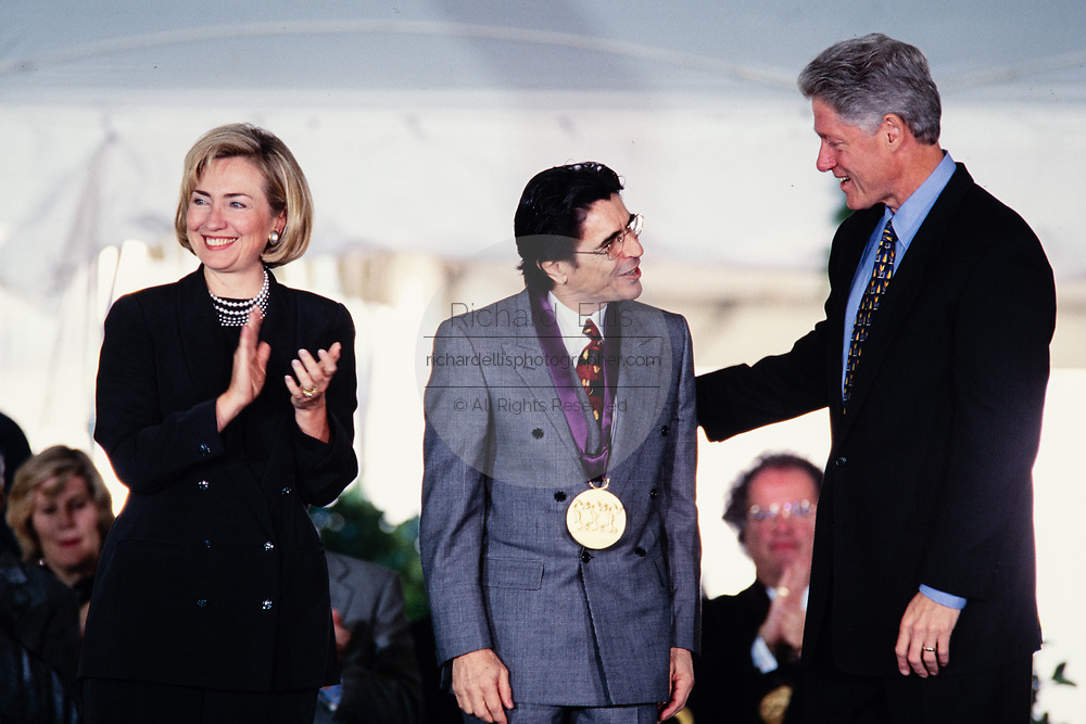 Dancer and artistic director of the Miami Ballet Edward Villella is presented the National Arts Medal by President Bill Clinton and First Lady Hillary Clinton during a ceremony on the South Lawn of the White House September 29, 1997 in Washington, DC.