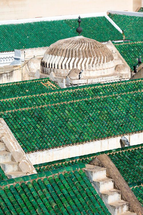 FEZ, MOROCCO - 3RD FEBRUARY 2018 - Green tiled roof on the Al-Kairouine Mosque and University, Fez Medina, Morocco.<br /> <br /> Established at the very beginnings of Morocco's oldest imperial city, the University of Al-Karaouine (also written as Al-Quaraouiyine and Al-Qarawiyyin) was founded in 859 and is considered by Unesco and the Guinness Book of World Records to be the oldest continually operating university in the world.<br /> <br /> Located in the heart of the old city, the complex is composed of a mosque, university and library, and is connected to the labyrinth of interconnecting streets and alleyways on all four sides. Its ceramic green tiled roofs take centre stage over Fez's urban sprawl from any viewpoint over the city.