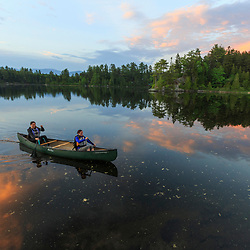 Two women canoe on Long Pond near the Appalachian Mountain Club's Gorman Chairback Lodge. Maine's 100 Mile Wilderness.