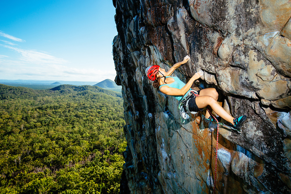 A female climber putting in some effort on the rock of the locally known 'Slider' on Mt Tibrogargan in Glasshouse Mountains National Park.