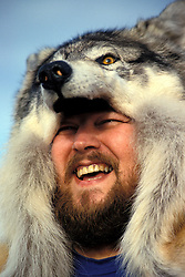 Alaska: Winter in Alaska.  Photo akwint102.  Man in wolf hat at Fur Auction..Photo copyright Lee Foster, 510/549-2202,  lee@fostertravel.com, www.fostertravel.com