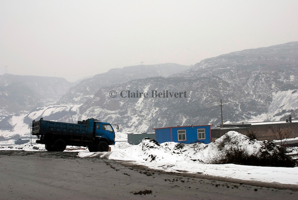 Coal truck on the back of a road. Days and nights hundreds of trucks are conveying coal. This Province is China's largest coal supplier with 500 millions of tonnes each year. It is also the most polluted of the country. Roads and trucks are covered with coal.