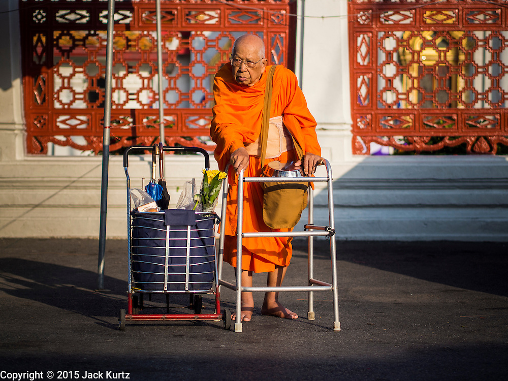 31 MARCH 2015 - BANGKOK, THAILAND: A monk with a walker at Wat Benchamabophit in Bangkok waits for Buddhist lay people to bring alms to the temple. Wat Benchamabophit Dusitvanaram, a Buddhist temple (wat) in the Dusit district of Bangkok, Thailand. Also known as the marble temple, it is one of Bangkok's best known temples and a major tourist attraction. It typifies Bangkok's ornate style of high gables, stepped-out roofs and elaborate finials. Monastic life at Wat Bencha differs from most other temples in that lay people come to the temple to present food and alms to the monks rather than the monks going out and walking through the community as they do at most other Thai temples.     PHOTO BY JACK KURTZ