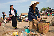 A woman is preparing to weigh fish on a scale at a transportation waypoint busy with activity near Pakse, Southern Laos.
