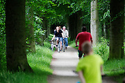 In Soest neemt een vader een kinder mountainbike mee aan de hand tijdens een fietstocht met het gezin.<br />