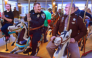 STILL KIDS AT HEART --- Logansport Police Department officer Flaude Dillon, left, and Cass County Sheriff Deputy Scott Turney, right, ride round and round on the historic Dentzel Carousel at Riverside Park in Logansport, Indiana, Sunday morning December 11, 2016, during the Shop With A Cop event that brought some Christmas cheer and gifts to needy area children. (J. Kyle Keener/Pharos-Tribune via AP)