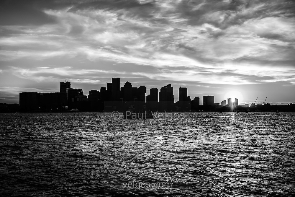 Boston sunset black and white photo with the Boston skyline and Boston Harbor. Boston Massachusetts is a major city along the Atlantic Ocean on the East coast of the United States.