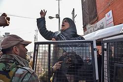December 18, 2018 - Srinagar, Jammu & Kashmir, India - Kashmiri Women activist seen shouting slogans inside a police vehicle after being detained by Indian policewomen during protest in Srinagar...Authorities imposed restrictions in many parts of the Kashmir valley to prevent the protest march called by Separatist leaders against the killings of seven civilians recently by Indian forces. (Credit Image: © Idrees Abbas/SOPA Images via ZUMA Wire)