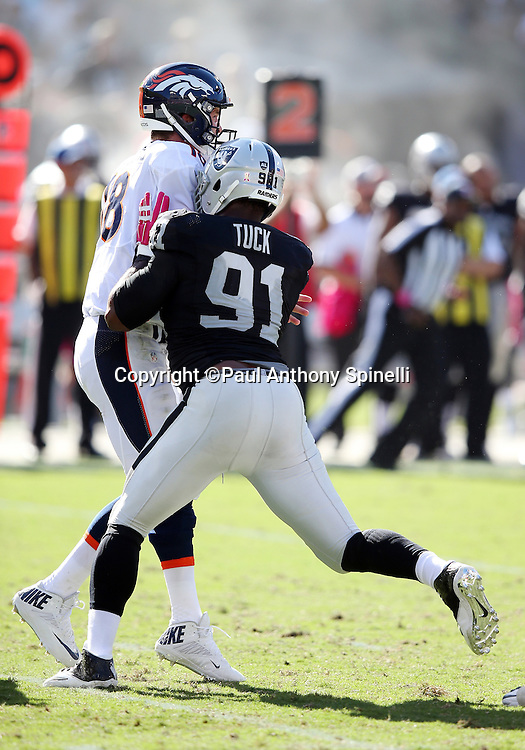 Oakland Raiders defensive end Justin Tuck (91) hits Denver Broncos quarterback Peyton Manning (18) during the 2015 NFL week 5 regular season football game against the Denver Broncos on Sunday, Oct. 11, 2015 in Oakland, Calif. The Broncos won the game 16-10. (©Paul Anthony Spinelli)