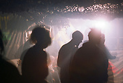 The Free Party and Teknival Scene from the Book 'Out of Order': Partying inside a tent, shadows of ravers dancing.