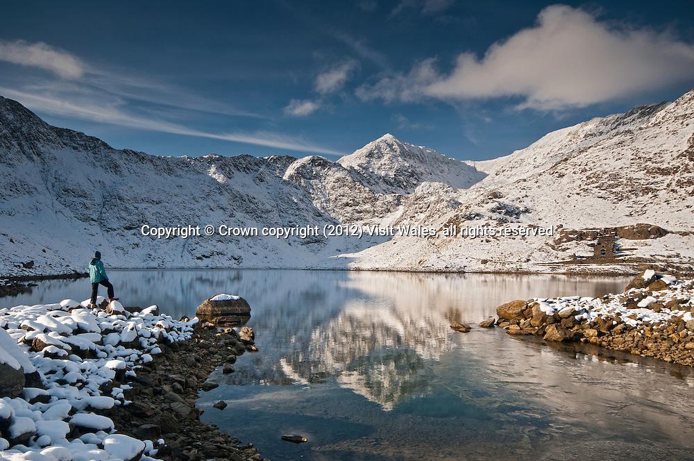 Walker looking towards snow-covered summit of Snowdon (Yr Wyddfa) from Llyn Llydaw lake<br /> Winter<br /> Snowdonia<br /> Gwynedd<br /> Mountaineering<br /> Walking<br /> Activities and Sports