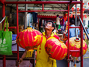 29 JANUARY 2019 - BANGKOK, THAILAND:       A worker hangs New Year lanterns at Wat Mangon Kamalawat, a large Chinese Buddhist temple in Bangkok's Chinatown district. Chinese New Year celebrations in Bangkok start on February 4, 2019. The coming year will be the Year of the Pig in the Chinese zodiac. About 14% of Thais are of Chinese ancestry and Lunar New Year, also called Chinese New Year or Tet is widely celebrated in Chinese communities in Thailand.      PHOTO BY JACK KURTZ
