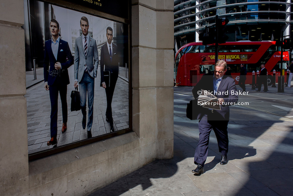 Man walks past a stylish clothing shop for businessmen people on a poster in the City of London.