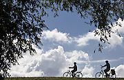Only as silhouette, two cyclists are to be recognized on the or dike in the Brandenburg, Germany, ride wine (MŠrkisch or country) on Thursday (17.07.2008). Photo: Patrick Pleul/lbn +++(c) dpa - report + + +