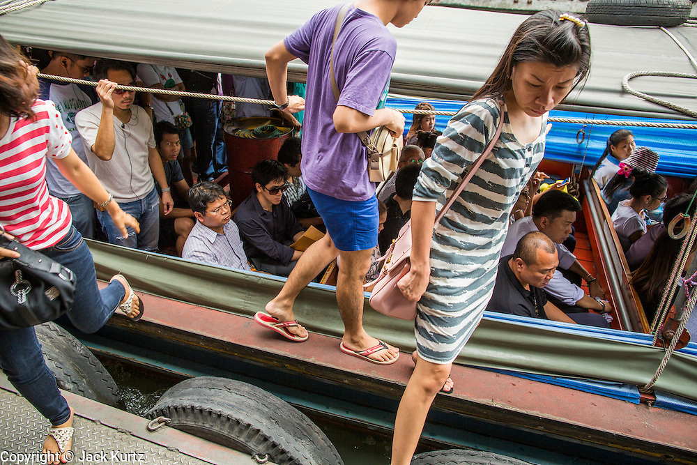 14 NOVEMBER 2012 - BANGKOK, THAILAND: Passengers get off and on a khlong boat at the Asoke Petchaburi Pier on Khlong Saen Saeb. Bangkok used to be criss crossed by canals (called Khlongs in Thai) but most have been filled in and paved over. Khlong Saen Saeb is one of the few remaining khlongs in Bangkok with regular passenger boat service. Boats and ships play an important in daily life in Bangkok. Thousands of people commute to work daily on the Chao Phraya Express Boats and fast boats that ply Khlong Saen Saeb. Boats are used to haul commodities through the city to deep water ports for export.      PHOTO BY JACK KURTZ