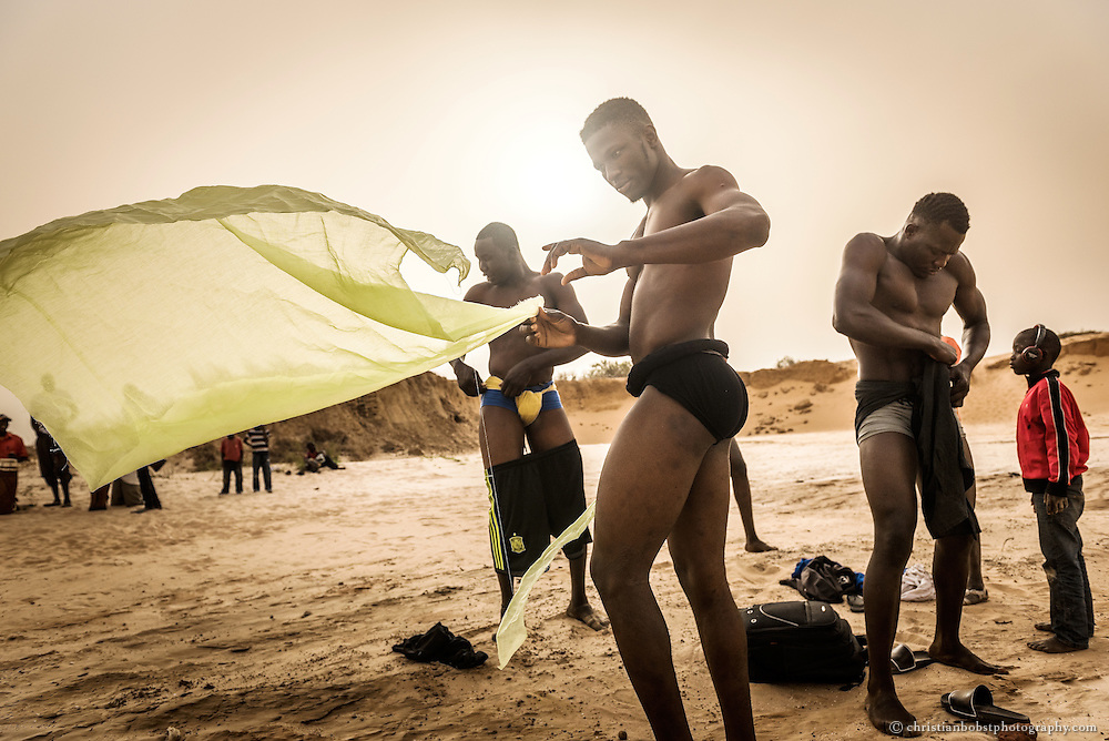 April 11, 2015. Young men prepare themselves for a wrestling fight in Bambilor, a small village close to Dakar. The wrestlers wrap a cloth around their abdomens at which the wrestlers hold each other during the fight.