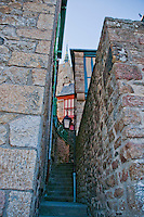 Looking up a steep alley past the original village buildings to the spire of the Mont St. Michel abbey.