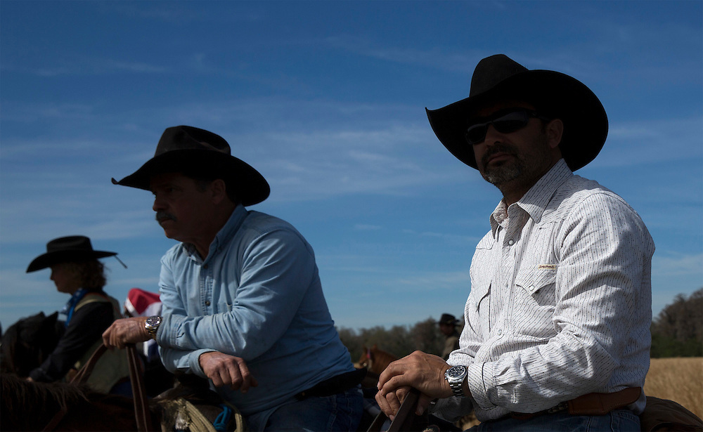 Two modern day Cow Hunters David Medina (center) and brother Delio Medina (right) of Miami take in the scene at the end of the Great Florida Cattle Drive '16. <br />