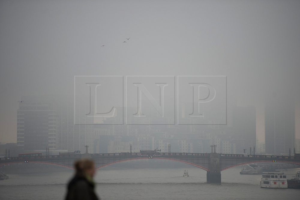 © London News Pictures. 21/01/2014. London, UK.  Building shrouded in fog behind Lambeth Bridge  in central London on January 21, 2014. Photo credit: Ben Cawthra/LNP