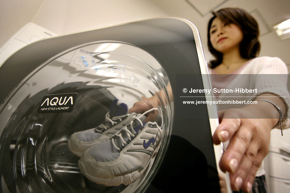 A demonstration by Sanyo of the Aqua Washing Machine, which for a full wash of clothes uses eight litres of water, compared with the usual 80-90 litres.  It can also deodorise clothes and shoes without using any water at all. Tokyo, Japan, Monday, June 18th, 2007.