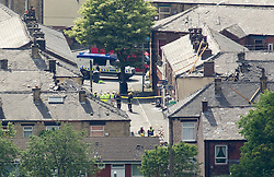 © Licensed to London News Pictures. 27/06/2012. Oldham , UK . A large explosion , believed to be caused by gas , has brought down at least one house in an Oldham terrace. GV of the scene taking from high above showing the gap where the destroyed houses used to stand and parts of damaged surrounding houses . Photo credit : Joel Goodman/LNP
