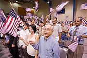 July 4, 2008 -- Phoenix, AZ: VOUNG PHAM, (RIGHT) originally from Vietnam, waves his American flag after he was naturalized a US citizen at a naturalization ceremony in Phoenix, AZ, Friday. About 300 people from 41 countries were naturalized as US citizens at South Mountain Community College, in Phoenix, AZ, Friday. It was the 20th year the college has hosted the Fiesta of Independence. More than 5,000 people have become naturalized US citizens at the Fiesta of Independence. More than 5,000 people have become naturalized US citizens at the Fiesta of Independence. The largest number of new citizens, 158, came from Mexico. There were also large numbers of new citizens from the Philippines, Bosnia-Herzegovnia and India.  Photo by Jack Kurtz