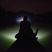 A honey hunter checking the way for the boat to cruise at man-made Pedu lake of GUMFC  in the darkness of the night, to return to their camping site after harvesting honey from near by forest on March 6, 2016.