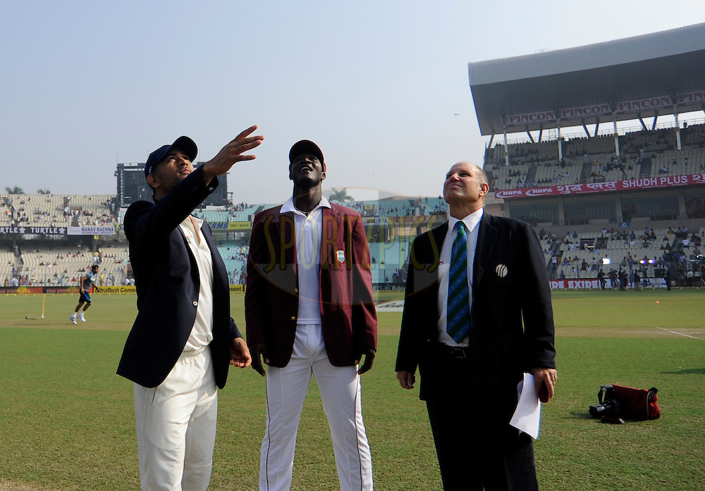 Mahendra Singh Dhoni captain of India and Darren Sammy captain of West Indies during the toss during day one of the first test match between India and The West Indies held at The Eden Gardens Stadium in Kolkata, India on the 6th November 2013<br /> <br /> Photo by: Pal Pillai - BCCI - SPORTZPICS