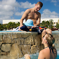 A mother and father play with their son in a resort pool.