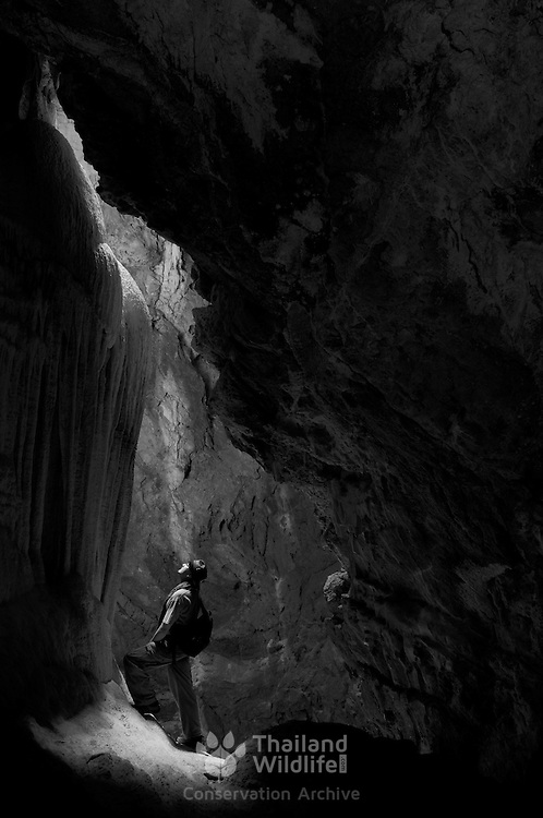 A hiker exploring the limestone formations in Sai Cave in the Khao Sam Roi Yot National Park in Thailand.