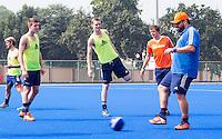 BHUBANESWAR (India) - Het Nederlands hockeyteam trainde vanmorgen op een bijveld van het Kalinga hockeystadion voor de wedstrijd van morgen tegen Pakistan voor het toernooi om de Champions Trophy. bondscoach Max Caldas met voetbal. Jelle Galema, Mirco Pruijser (m) en Constantijn Jonker kijken toe. ANP KOEN SUYK