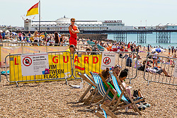 © Licensed to London News Pictures. 12/07/2020. Brighton, UK. Members of the Brighton Lifeguards stand watch over the beach in Brighton And Hove as sunny and warm weather is hitting the seaside resort. Photo credit: Hugo Michiels/LNP