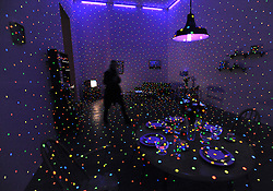 "© Licensed to London News Pictures. 07/02/2012, London, UK. The installation,  ""I'm Here, But Nothing 2000/2012' The installation is made up of a room covered in vinyl stickers, ultraviolet fluorescent lights, furniture and household objects. Press preview of Yayoi Kusama at the Tate Gallery Bankside today 7th February 2012. The exhibition spans six decades of the artists work. Kusama is one of Japan's best known living artists.  Photo credit : Stephen Simpson/LNP"