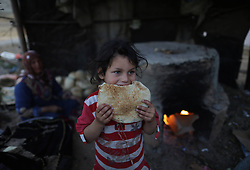 59581097  .A Palestinian refugee girl eats freshly baked bread in front of her family house in a poverty-stricken quarter in northern Gaza Strip town Beit Lahiya on April 28, 2013. Reports said that an increasing number of Gazan families are falling further into poverty, with unemployment rates at over 30 percent according to 2012 estimates, on April 28, 2013, 29, April 2013. Photo by: i-Images.UK ONLY